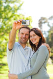 Couple taking a photo of themselves in the park Royalty Free Stock Image