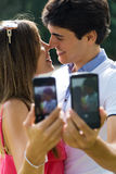 Couple taking photo of themselves with smart phone on romantic p Royalty Free Stock Photos