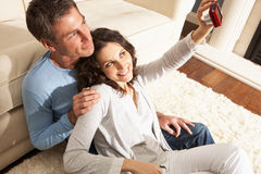 Couple Taking Photograph On Digital Camera At Home Royalty Free Stock Image