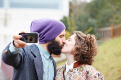 Couple taking a photograph of themselves kissing with a smartpho Stock Images