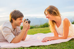 Couple taking photos of each other with retro vintage camera on Royalty Free Stock Photography