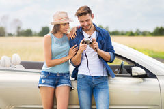 Couple taking photos while out on a road trip. Young couple standing near convertible Stock Image