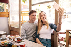 Couple taking photos of themselves in cafe Stock Image