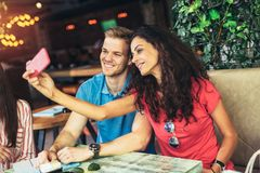 Couple taking photos of themselves with mobile phone. In cafe Stock Image