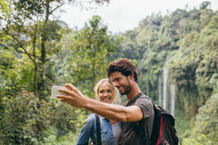 Couple taking picture in front of waterfall stock photo
