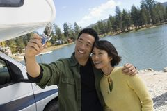 Couple taking picture of selves outside RV at lake Royalty Free Stock Photo