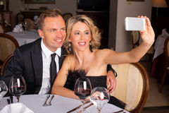 Couple taking a picture of themselves at restaurant Stock Photos