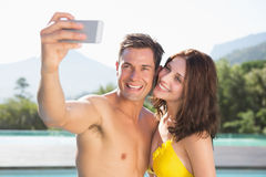 Couple taking picture of themselves by swimming pool Stock Photography