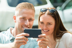 Couple Taking Picture Using Mobile Phone Stock Image