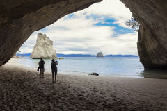 Couple taking pictures at scenic Cathedral Cove New Zealand. Beautiful and scenic New Zealand. People taking photos at Cathedral Cove Stock Images