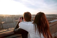 Couple taking pictures of the sunset on rooftop of the city Royalty Free Stock Photos