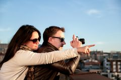 Couple enjoys taking pictures of the sunset on the rooftop Royalty Free Stock Image