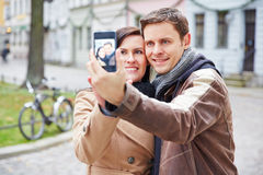 Couple taking self portrait in city Stock Photography