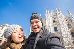 Couple taking self portrait in Duomo square in Milan. Winter holidays, traveling and relationship concept royalty free stock image