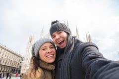 Couple taking self portrait in Duomo square in Milan. Winter traveling, Italy and relationship concept. Couple taking self portrait in Duomo square. Concept royalty free stock photos