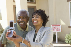 Couple Taking Self-Portrait In Front Of New House royalty free stock image