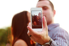 Couple taking self-portrait. Photos with mobile smart phone Royalty Free Stock Photo