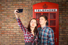 Couple Taking Self Portrait with Red Phone Booth Royalty Free Stock Photo