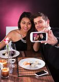 Couple taking self portrait at restaurant. Smiling young couple taking self portrait through smartphone at restaurant table Stock Photos