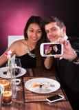 Couple taking self portrait at restaurant Stock Photos