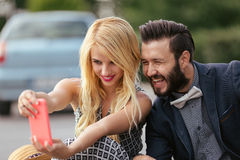 Couple taking self portrait on a smart phone Royalty Free Stock Photography