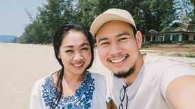 Couple is taking selfie on the beach. Asian couple is taking selfie on random beach of Thailand Stock Photo