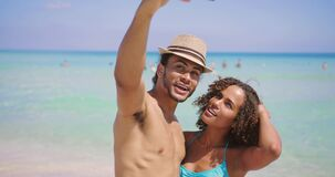 Couple taking selfie on beach. Cheerful ethnic man and woman kissing and taking selfie with smartphone on beach at the ocean stock video footage