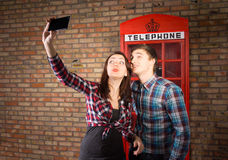 Couple taking a selfie with a British phone booth Royalty Free Stock Photo