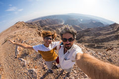 Couple taking selfie at the Fish River Canyon, scenic travel destination in Southern Namibia. Fisheye view from above in backlight.  royalty free stock images