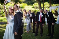 Couple taking selfie with guests during wedding. In park royalty free stock photography