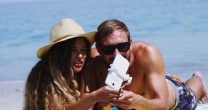 Couple taking selfie from mobile phone at beach. On a sunny day stock footage