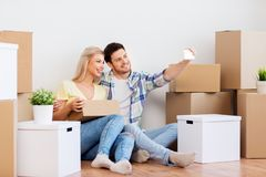 Couple taking selfie and moving to new home. Moving, people and real estate concept - smiling couple with big cardboard boxes taking selfie by smartphone at new royalty free stock photo