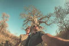 Couple taking selfie near Baobab plant in the african savannah with clear blue sky. Fisheye view from below, toned image. Wilderne Stock Image