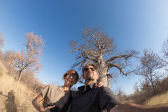 Couple taking selfie near Baobab plant in the african savannah with clear blue sky. Fisheye view from below. Wilderness safari and Stock Images