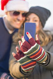 Couple taking selfie outdoors waring Christmas hats Stock Photography
