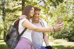 Couple Taking Selfie Outside. Young couple taking selfie portrait in the park Stock Images