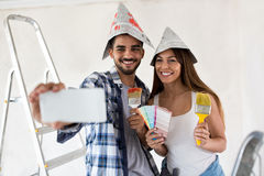 Couple taking selfie while painting home. Attractive couple taking selfie while painting home stock photos