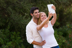 Couple taking selfie photo with digital tablet. Camera hole moved from the corner to the center on the top Stock Photo