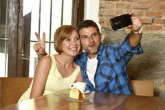 Couple taking selfie photo with mobile phone at coffee shop smiling happy in romance love concept Stock Images