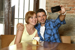 Couple taking selfie photo with mobile phone at coffee shop smiling happy in romance love concept Stock Photo
