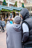 Couple taking a selfie photo. Seattle, WA, USA Dec. 3, 2016: Couple holding phone out while composing a selfie photo of themselves during Christmas time at Pike Royalty Free Stock Images