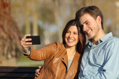 Couple taking selfie photo sitting in a bench Stock Photo