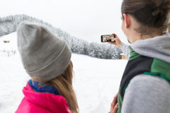 Couple Taking Selfie Photo On Smart Phone Snowy Village Wooden Country House Man Woman Winter Snow. Resort Cottage Royalty Free Stock Image