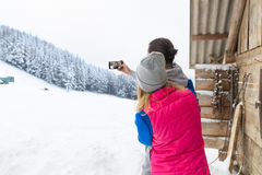 Couple Taking Selfie Photo On Smart Phone Snowy Village Wooden Country House Man Woman Winter Snow. Resort Cottage Stock Image