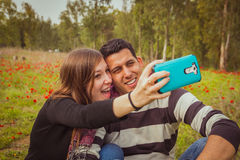 Couple taking selfie picture with their mobile phone in field of stock photography