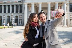 Couple taking selfie at prado museum madrid. Couple of tourists, a men and a woman, taking selfie in front of prado museum, in the city of Madrid, Spain royalty free stock photos