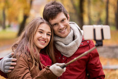 Couple taking selfie by smartphone in autumn park Royalty Free Stock Images