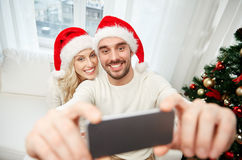 Couple taking selfie with smartphone at christmas Stock Photography