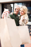 Couple taking selfie on smartphone with shopping bags on street Stock Images