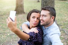 Happy couple taking selfie photos sitting in a bench in a park Stock Photo